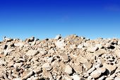 Pile of rock rubble hardcore background with a blue sky and copy space for construction ecology ideas and designs poster