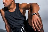 cropped shot of young african american sportsman wearing fitness tracker on grey poster