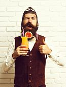 handsome bearded aviator man with long beard and mustache on satisfied face holding glass of alcoholic cocktail in vintage suede leather waistcoat with hat and glasses on white brick wall background poster