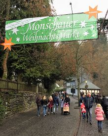 Monschau, Germany - December 17, 2016: Shoppers walk under a sign marking the annual Monschau Christmas market in Germany