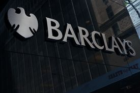 NEW YORK, NEW YORK - July 2, 2014: Sign on exterior of Barclays Capital in New York City with reflection of people walking by. Barclays is a British multinational bank and financial services company