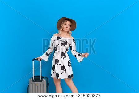 Young blond curly woman in a white dress and sundown hat with grey luggage bag is excited at sightseeing tour while standing infront of a blue background. Concept of traveling poster