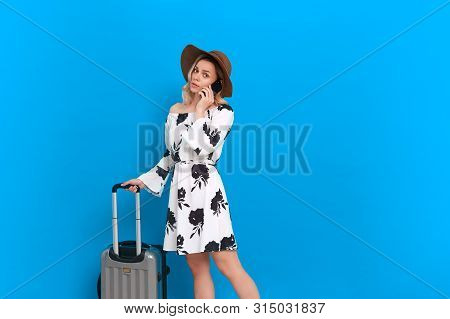 Young blond curly woman in a white dress and sundown hat with grey luggage bag speaks on the phone standing infront of a blue background. Concept of traveling poster