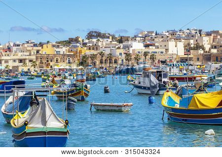 Maltese Boats Float In The Harbor Of Marsaxlokk, Malta. The Fishing Boats Are Decorated With The Eye