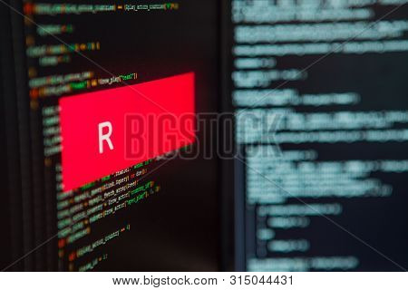 Programming Language, R Inscription On The Background Of Computer Code. Modern Digital Technologies