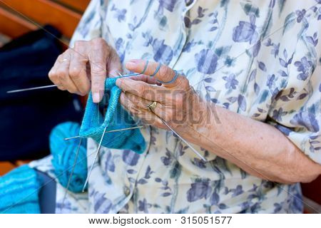 Pensioner, Retiree Concept, Old Retiree Woman In Her Spare Time Knits Socks For Her Grandchildren, T