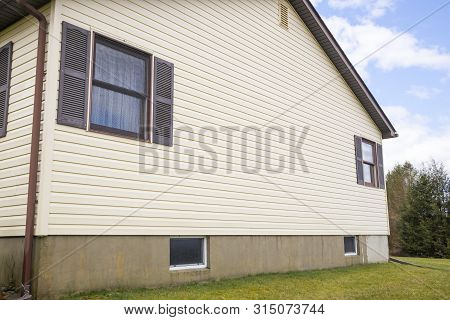 House With Pale Yellow Vinyl Siding In Suburbia