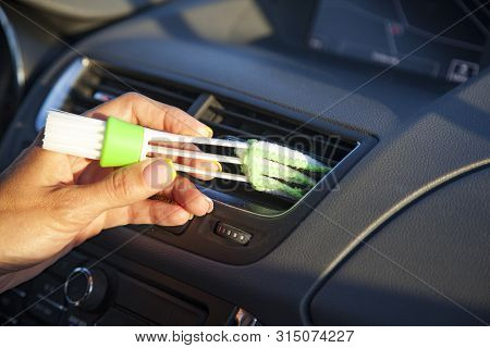 Female Hand With A Brush For Wiping Dust On The Dashboard Of The Car, A Brush To Remove Dust In The