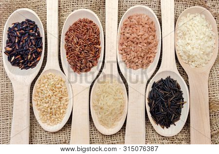 Assortment Of Different Rice In Wooden Spoons: White Rice Red Rice Black Rice A Mixture Of Wild And