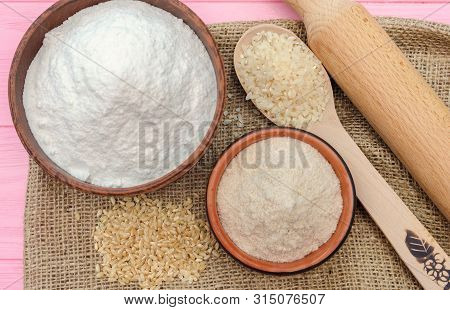 Whole grain rice flour and white rice flour in bowls. White rice, brown rice. The whole grain of rice. Unpolished rice in wooden spoon. Healthy food rice background. Row rice. Rice flour. Rice flour baking