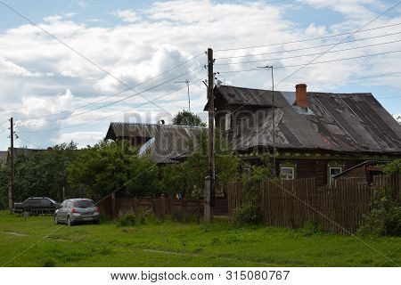 Yuryevo-devichye, Russia - July 07, 20197: View Of Old Wooden Houses And Modern Cars On A Rural Stre