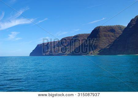 Na Pali Coastline, On The Island Of Kauai, Hawaii, Is Rugged And Steep.  Steep Cliffs Meet Vivid Blu