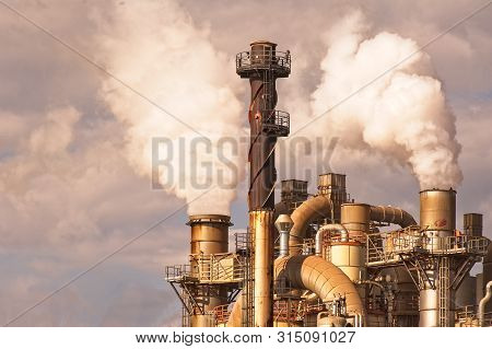 Industrial Plant With Smoking Smokestack,tubes,silos.