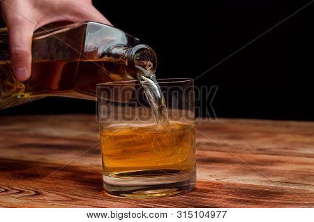 From A Decanter, Whiskey Is Poured Into A Glass.