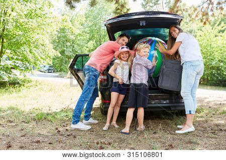 Happy family stows luggage in the car trunk before traveling on vacation