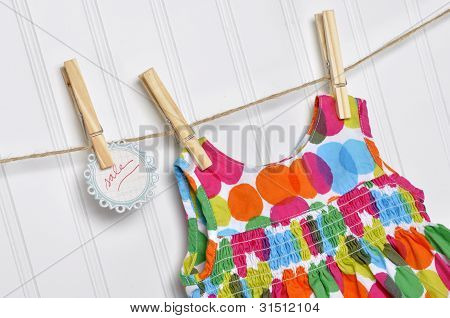 Polka Dot Baby Dress On A Clothesline With Handwritten Sale Sign.