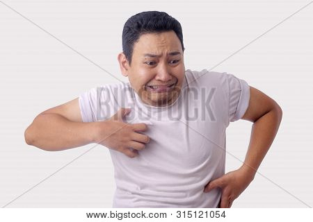 Portrait Of Young Asian Man Feel Itchy, Scratching His Body In Pain