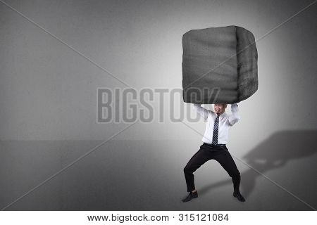 Composite Image. Stress Overwork And Pressure In Business Concept. Businessman Holding Heavy Stone O