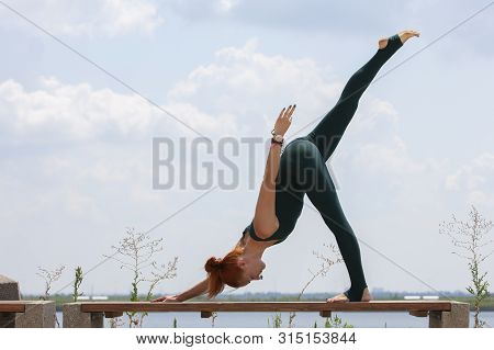 Picture Of Young Fitness Lady Outdoors In The Beach Make Yoga Stretching Exercises.