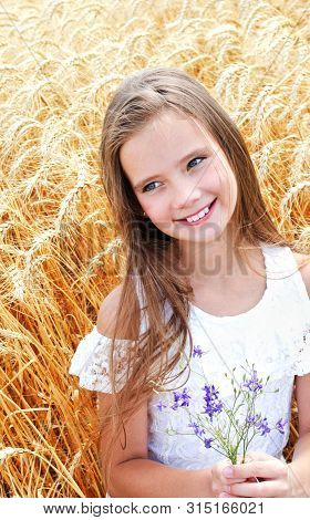 Portrait Of Smiling Cute Little Girl Child On Field Of Wheat Holding Flowers Outdoor