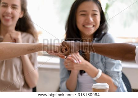 Multiracial Caucasian And African Buddies Fist Bumping Greeting