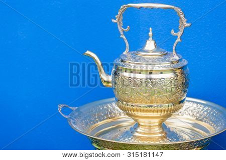 Traditional Moroccan Tea Pot Against Bright Blue Background