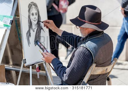 Prague, Czech Republic - May 8, 2019: Street Artist Creating His Art Painting Portrait Of A Young Gi