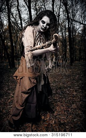 Halloween Theme: Wicked Creepy Voodoo Witch Attacking By Stick. Portrait Of The Evil Hag In Dark For