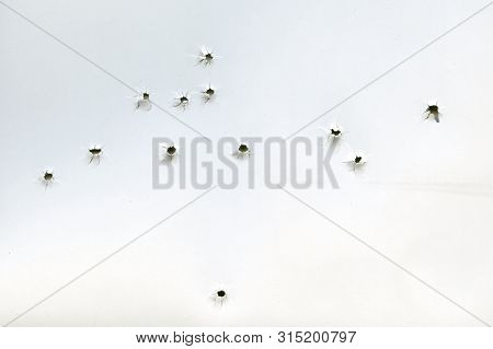 Bullet Holes On A White Sheet Of Paper, View From The Inside, Gunshot Damage, Abstract Background.