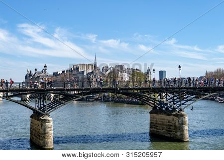 Paris, France - March 30, 2019: People Walking On Pont Des Arts Bridge On The Seine River With Barge