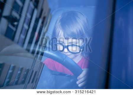 Driving Shool. Humorous Photo Of Cute Little Child Girl Learns To Drive.