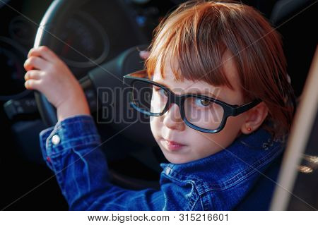 Driving Shool. Humorous Portrait Of Little Child Girl Learns To Drive.