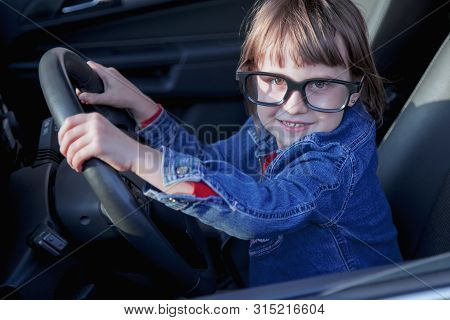 Driving Shool. Humorous Portrait Of Beautiful Little Child Girl Learns To Drive.
