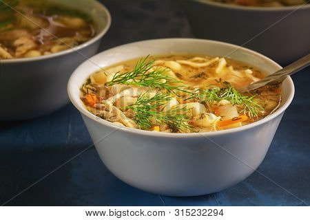 Nourishing Chicken Noodle Soup White Bowl Closeup. Full Dish Of Starter Meal. Healthy Family Recipe.