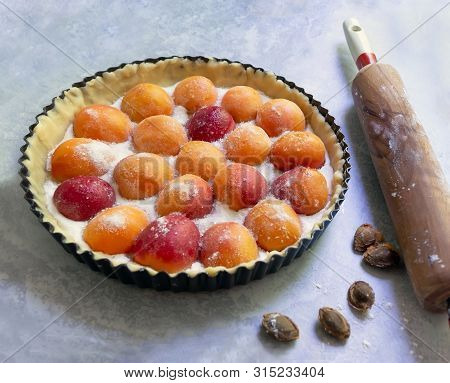 Homemade Raw Apricot Tart In Baking Dish, Apricot Pits And Rolling Pin.