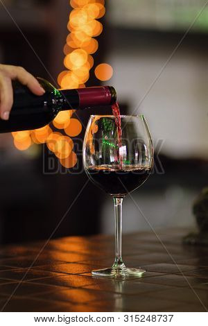 Red Wine Pouring Into Wine Glass. Shallow Depth Of Field. Bokeh. Warm Toning. Space For Text. Concep