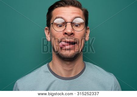 Portrait Of A Funny Young Man In Glasses Funny Sticking His Tongue Out And Squinting Eyes On A Green
