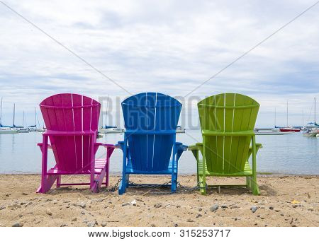 Multicoloured Muskoka Cottage Beach Chairs On The Sand Looking Out To The Harbor