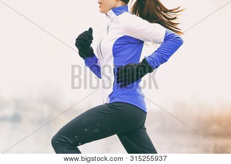 Winter running woman runner jogging in cold weather activewear clothing. Sport exercise person training cardio outdoors in snow.