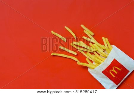 Mcdonalds French Fries In Small Paperbag On Bright Red Background