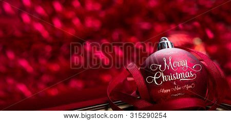Merry Christmas And Happy New Year Red Background.close Up Red Decoration Ball With Blur Tinsel At B