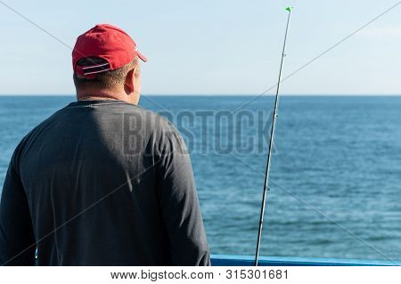 Fisherman Fishing From Pier. Man With Fishing Rod In Red Cap. Windless Weather, Calm. Copy Space. Ri