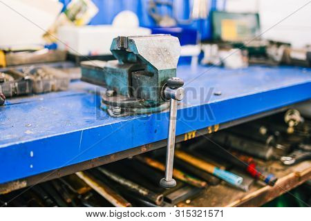 Vise blue in the workshop. Joiner tools for fixing parts for various types of processing. Metal clamps. poster