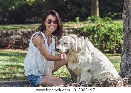 Cheerful Young Dog Lover Sitting With The Dog In Summer Park. Beautiful Girl Wearing Stylish Sunglas