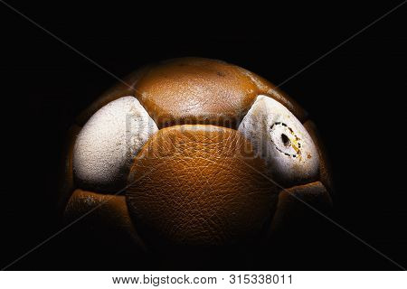 Closeup View Of An Old Soccer Ball In Dark.