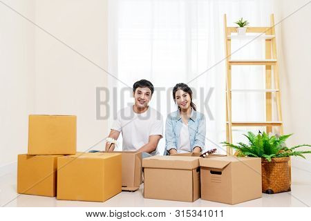 Portrait Of Young Attractive Happy Asian Couple Man And Woman Sitting At New Home Smiling To Camera