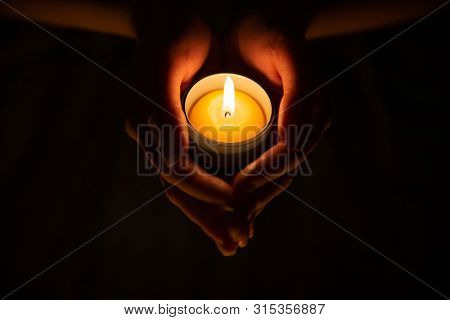 Lighted Candle In Female Hands In The Dark On The Black Background. Diwali, Obon Festival
