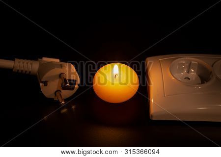 Burning Yellow Candle, White Contact Plug And White Socket Are In Dark On The Black Table/background