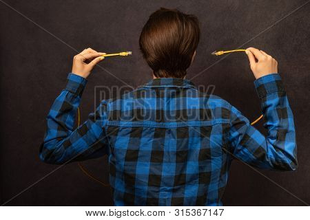 Woman In Checkered Shirt Is Standing On The Back View And With Both Hands Are Inserting Yellow Usb W