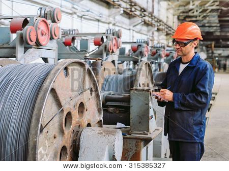 Wire Rod, Fittings In Warehouses. Worker Alongside A Bundle With Catalkoy. Industrial Storehouse At